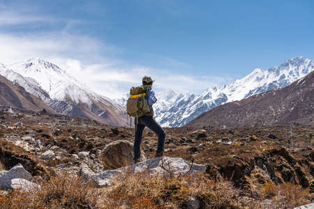 Young Asian woman trekker with backpack trekking in Langtang valley, A woman traveling in Himalaya mountains range in Nepal, Asia