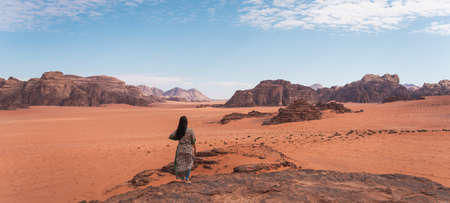 Young Asian traveller with local Arab dress standing on top of mountain and enjoying landscape of Wadi Rum desert, Jordan, Arab, Asia. Panoramic banner portion