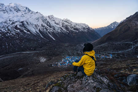 Young woman trekker sitting on rock on top of Kyanjin Ri view point in a morning sunrise, Himalaya mountains range, Nepal, Asia