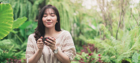 Young Asian woman relaxing in garden with a cup of coffee in a morning. A woman inhaled coffee. Panoramic banner portion. Bangkok, Thailand