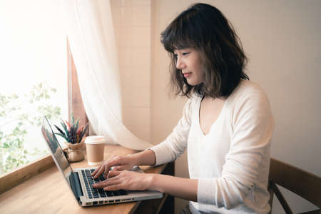 Young Asian woman working online with laptop computer with a cup of coffee on wooden table. A woman with smiley face working from home. Social distancing concept. Bangkok, Thailand