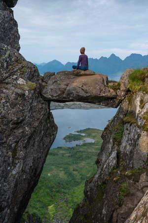 Asian woman sitting on Djevelporten or Devil's gate in Floya mountain hiking trail in summer season. Svolvaer fishing village in Lofoten island, Scandinavia, Europe