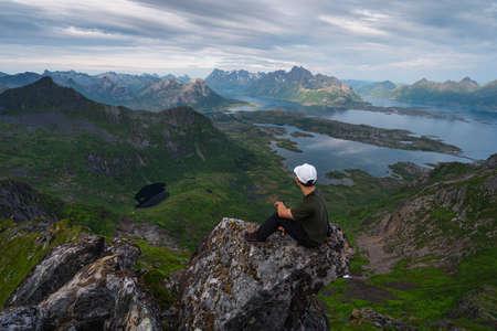 Young Asian man trekker sitting on rock on top of Floya mountain peak in Lofoten island in summer season, Northern Norway, Scandinavia, Europe 版權商用圖片