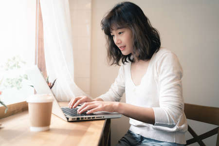Young Asian woman working with laptop computer and drinking a cup of coffee. A happy woman with smiley face working from home. Social distancing concept. Bangkok, Thailand 版權商用圖片