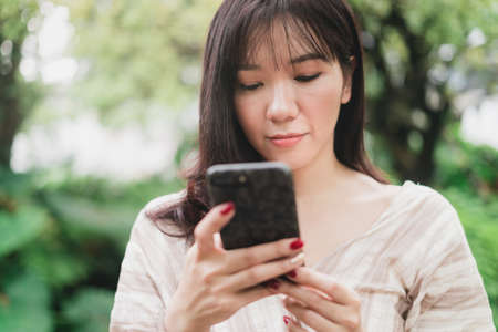 Young Asian woman using smart phone for chating or seaching information. A woman with smiley face in greeny garden. Digital lifestyle concept. Bangkok, Thailand