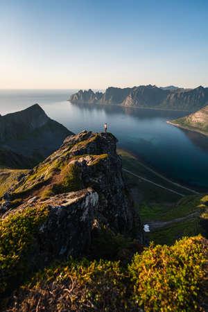 A woman standing on top of Husfjellet mountain peak in Senja island in summer season, Norway, Scandinavia 版權商用圖片