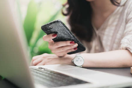 Close up hands of woman using smartphone for searching online information in garden. Technology business and social distancing concept. Bangkok, Thailand
