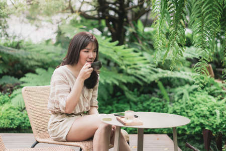 Young Asian woman sitting and drinking  a cup of coffee in a garden. A woman enjoying natural outdoor lifestyle. Bangkok, Thailand