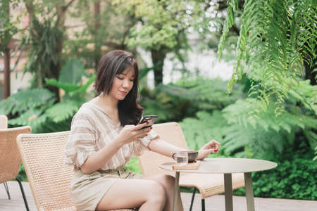 Young Asian woman using smart phone for chating or seaching information. A woman with smiley face in greeny garden. Bangkok, Thailand