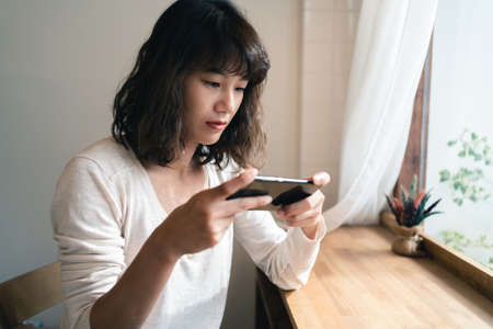 Close up of young Asian woman using smartphone watching video clip and playing online game. Technology business and social distancing concept. Thailand 版權商用圖片