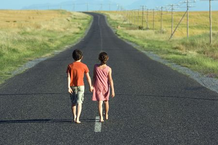 walking down: Little boy and girl, walking hand in hand down endless tarred road Stock Photo