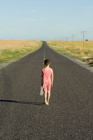 Young girl, aged seven, wearing a dress, walking down an endless road. photo