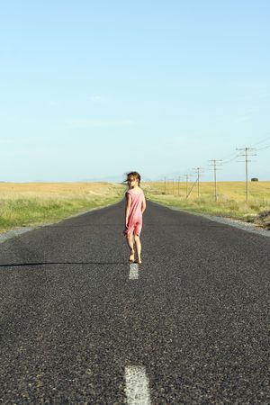 road shoulder: Little girl, aged seven, wearing a pink dress, walking down a tarred road and looking over her shoulder