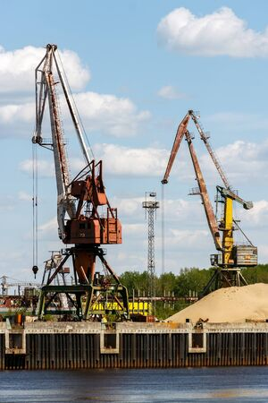 Port cranes unload sand in the district of the Bor glass plant