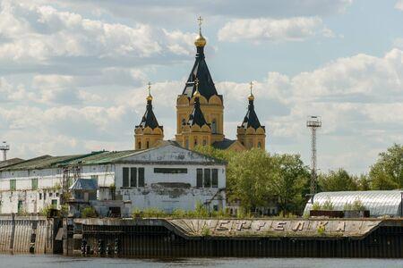 oka: Alexander Nevsky Cathedral in Nizhny Novgorod behind the buildings of the cargo river port on the Strelka Stock Photo