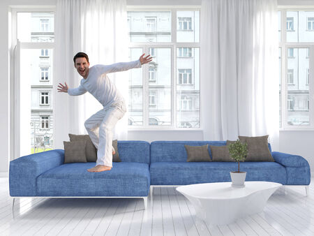 contemporary: Picture of freaky man dancing on a blue couch Stock Photo