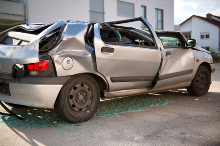 flattened: Completely wrecked silver hatchback sedan car with a flattened roof, shattered windows and buckled coachwork standing upright in the road surrounded by shattered glass shards following an accident