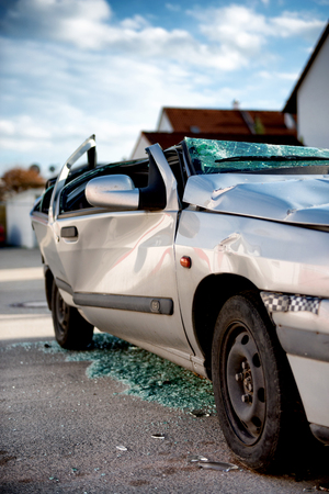 coachwork: Silver sedan car written off in a traffic accident standing in the road surrounded by shattered glass from its destroyed windscreen and windows, with a flattened roof and crumpled coachwork