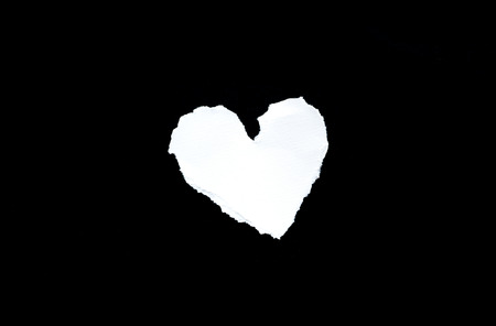 altruism: Trozo de papel blanco en forma de corazón sobre fondo negro Foto de archivo