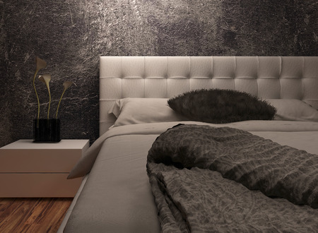 downlight: White huge bed standing against dark black wall Stock Photo
