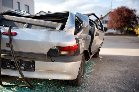 write off: Totaled hatchback motor vehicle after a smash viewed from behind showing a flattened roof and shattered windows as though it rolled over with glass shards underneath and bent and buckled bodywork Editorial