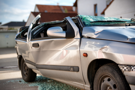 write off: Totally destroyed silver sedan motor car in a traffic accident with a flattened roof, shattered windows and crumpled bodywork Editorial