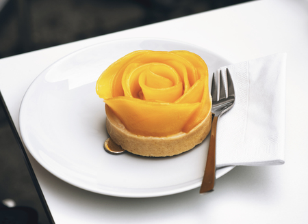 Rose shaped gourmet apple tart on a baked pastry base served on a plate for dessert in an upmarket restaurant photo