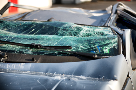 has been: Close up of the shattered windscreen and wipers of a car that has been involved in an accident