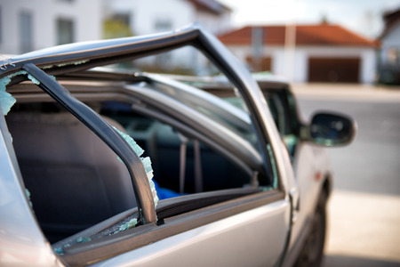 mva: Silver sedan car written off in a traffic accident standing in the road surrounded by shattered glass from its destroyed windscreen and windows, with a flattened roof and crumpled coachwork