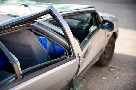 write off: Silver sedan car written off in a traffic accident standing in the road surrounded by shattered glass from its destroyed windscreen and windows, with a flattened roof and crumpled coachwork