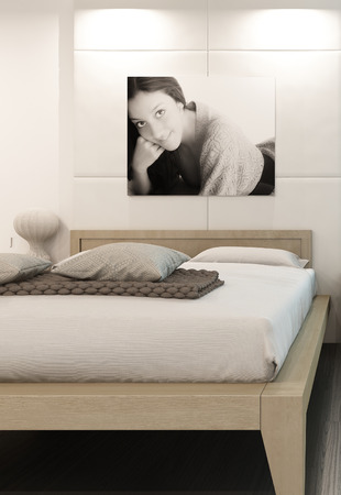 Comfortable bedroom interior with wooden bed and portrait of girl on wall photo