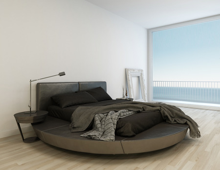 Black bed with bedsheets in front of huge window with seascape view photo