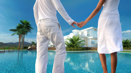 hands holding house: View from behind of a romantic couple standing holding hands overlooking their dream modern whitewashed tropical villa and sparkling swimming pool, torsos only in a conceptual image