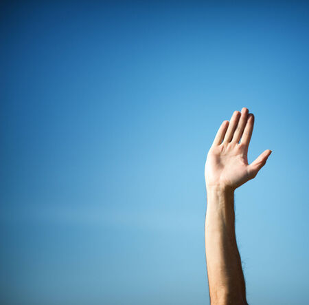 Raising hand with hand palm against pure blue sky