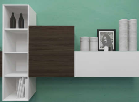 White wooden shelving on a green wall displaying a womens portrait, cylindrical containers or vases and bottles with a central black closed unit Stock Photo