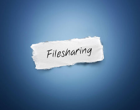 3d rectangular scrap of torn white paper with the word - Filesharing - in script resembling handwriting on a blue background with a vignette and copyspace photo