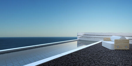 Patio landscaped with pebbles with a swimming pool and comfortable seating overlooking the ocean against a blue sunny sky photo