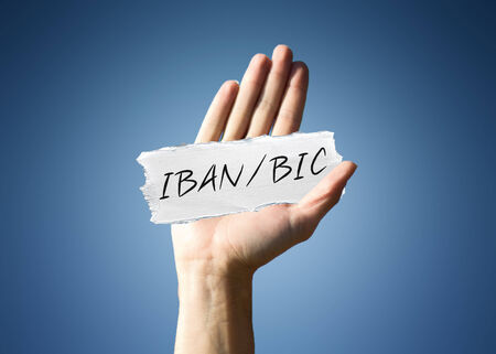 international bank account number: Man holding up a scrap of white paper with the words - IBAN  BIC - in script, close up of his hand on a blue background with a side vignette in a conceptual image