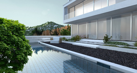 Modern luxury house with panoramic view windows overlooking a patio laid to pebbles with swimming pool and a mountain peak in the background photo