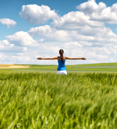 outspread: Image of a girl in a wheat field standing in the distance with her back to the camera and her arms outspread in celebration of a beautiful sunny summer day and freedom