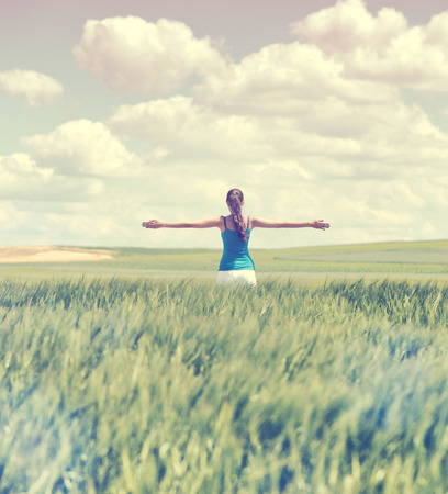 outspread: Faded retro style image of a girl in a wheat field standing in the distance with her back to the camera and her arms outspread in celebration of a beautiful sunny summer day and freedom Stock Photo
