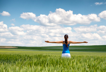 Image of a girl in a wheat field standing in the distance with her back to the camera and her arms outspread in celebration of a beautiful sunny summer day and freedom photo
