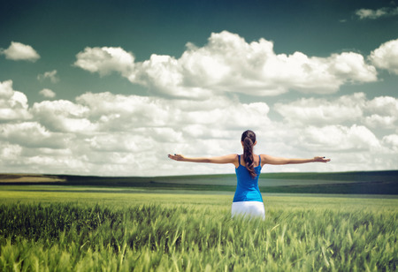 rejoices: Toned dramatic image of a girl in a wheat field standing looking away from the camera with outspread arms as she rejoices her freedom and the beauty of the clouds and nature