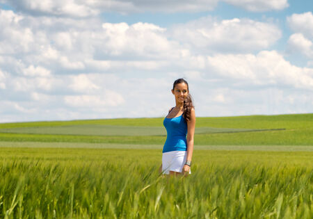 open air: Happy carefree young woman in a green wheat field smiling as she trails her hand through the young plants, low angle distance view with copyspace against a beautiful blue sky with fluffy white clouds Stock Photo