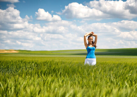 above head: Beautiful girl relaxing in a green wheat field standing with her arms raised above her head and a lovely serene smile against a pretty blue summer sky with fluffy white cloud Stock Photo