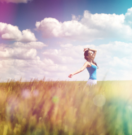 Woman frolicking in a summer field with colorful flare effect in rainbow or spectral colors under a cloudy blue sky, square format photo