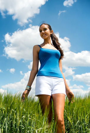 Low angle view of a beautiful tanned shapely young woman in shorts standing in a field of long green grass looking to the side with a lovely smile against a sunny cloudy blue sky Stock Photo