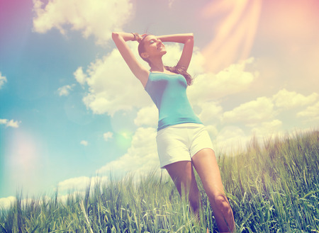 Young woman enjoying the warm summer sun standing in a green field with her head raised to the colorful rays with a smile of pleasure, colored flare filter effect photo