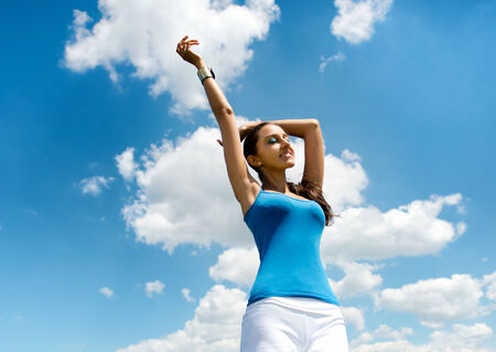 Beautiful busty young woman rejoicing in the sun standing against a sunny blue summer sky with fluffy white clouds with raised arms and a smile of bliss and pleasure