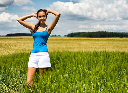 Beautiful girl relaxing in a green wheat field standing with her arms raised above her head and a lovely serene smile against a pretty blue summer sky with fluffy white cloud Stock Photo